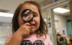 A preschool student looks through a magnifying glass.