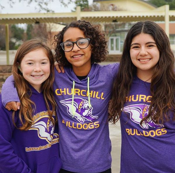 Three Churchill students in school shirts