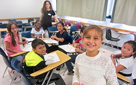 Photo of Cottage Elementary students smiling at the desks on campus of Sacramento State.