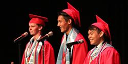 Photo of three graduates on stage