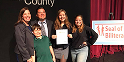 Student posing with family with seal of biliteracy award