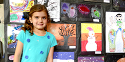 Child standing in front of a wall covered with student art
