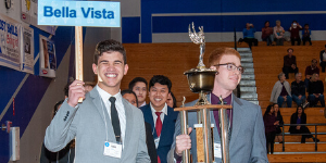 Students hold a Bella Vista sign and a trophy