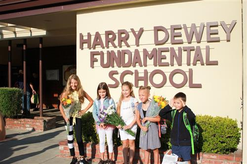Students outside Dewey Elementary sign