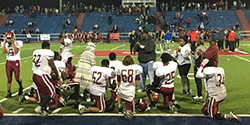 Photo of Encina football team taking a knee