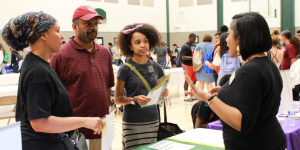 Student and parents talking with HBCU rep at booth