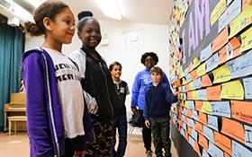 Students at Cameron Ranch look at a wall of diversity filled with student statements