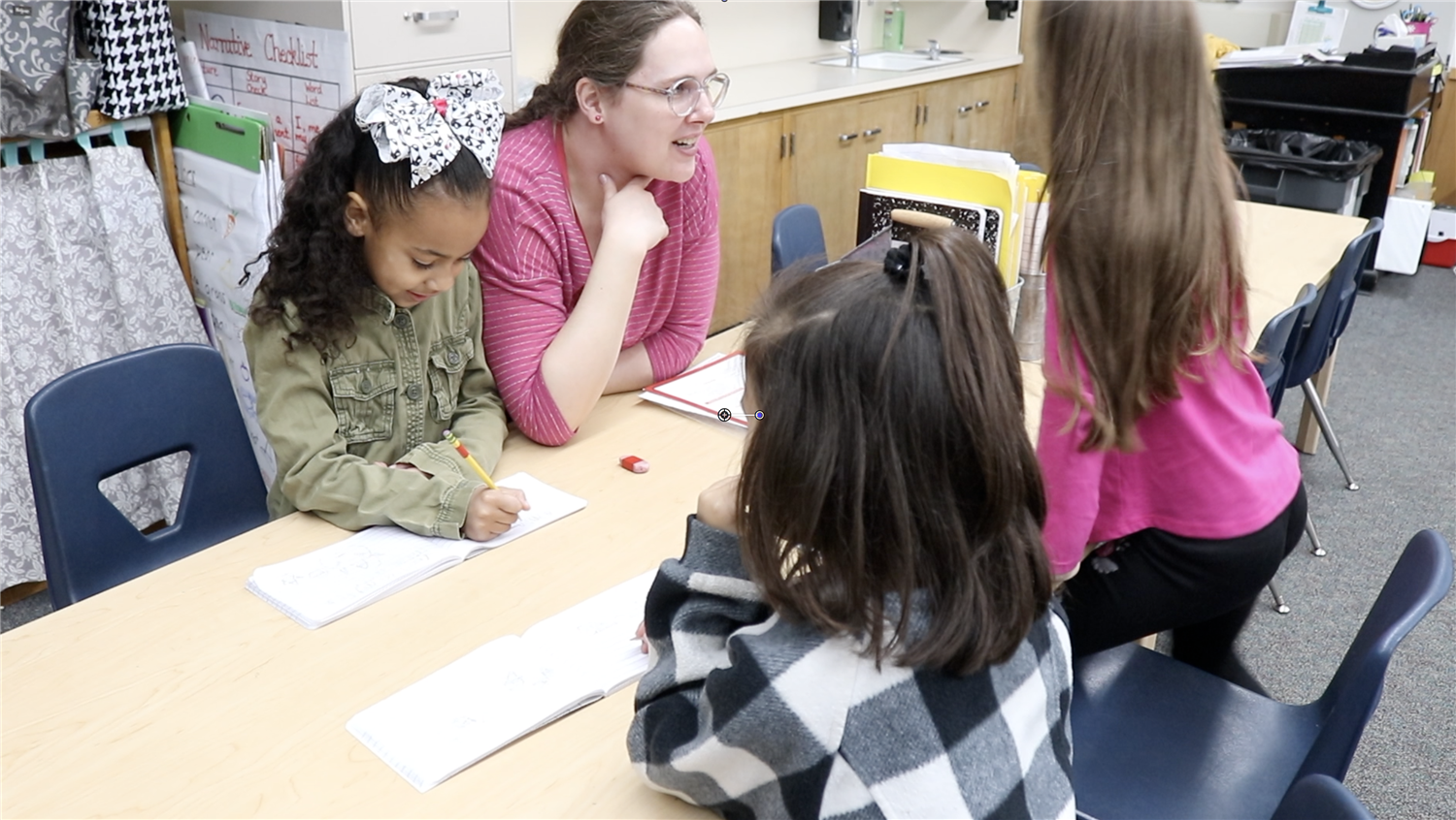 Teacher at Coyle Avenue Elementary School helps a small group of students with reading comprehension