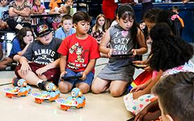 Summer school students demonstrate robots they coded to play a song