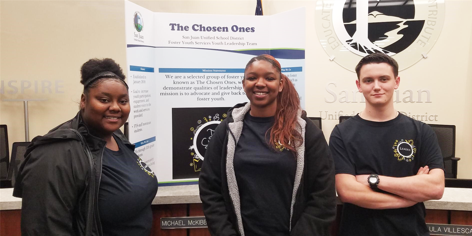 Three students in front of The Chosen Ones poster