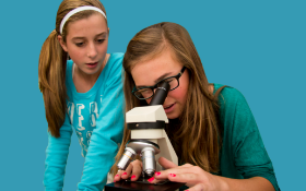 Two female students looking into microscope
