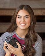 Female with brown hair holding camera