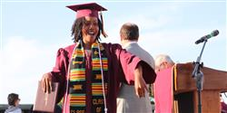 Photo of female Encina graduate crossing stage
